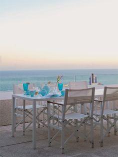 Céu e mar se encontram sem que nada atrapalhe a visão. Na mesa com tampo de Corian, a louça captura o azul da paisagem. O piso é de placas de concreto com pedriscos.