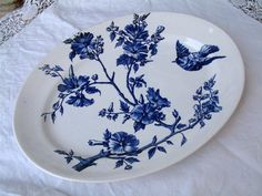 This is a stunning french antique indigo blue (purplish blue) Longchamp oval serving platter. It features a small bird in flight and flowers branching