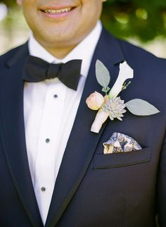Dapper navy suit with a bowtie and pretty boutonniere