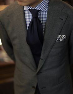 gray suit. blue gingham oxford. navy blue satin tie. patterned pocket square. sophisticated. corner office. style.
