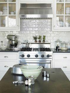 High gloss white brick/subway tile backsplash, shiny stainless hood and glass display cabinets