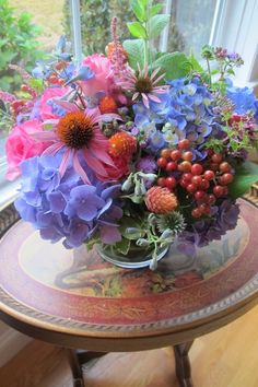 Lovely color combinations in this floral arrangement of coneflower, hydrangea, roses and grapes
