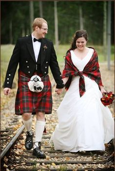 Groom wearing a kilt, and the bride has a shrug that is in the same color of tartan. Very good idea, since he has said he wants to wear a kilt when we get married.