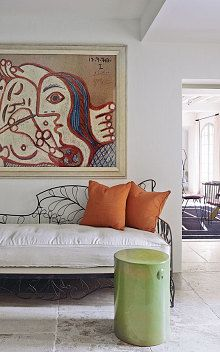 A Picasso lithograph hangs above an iron day-bed and ceramic stool by Emerie et Cie