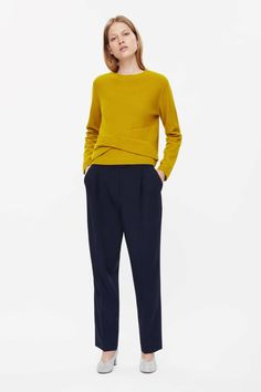 This jumper is made from soft wool with a textured feel with a twisted panel detail at the front. A loose, relaxed fit, it has long sleeves, tightly ribbed edges and a simple round neckline.