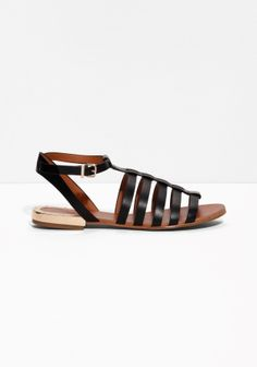Polished metal cuff encircles the heels of these easygoing leather sandals with a strappy upper and a buckled ankle strap.