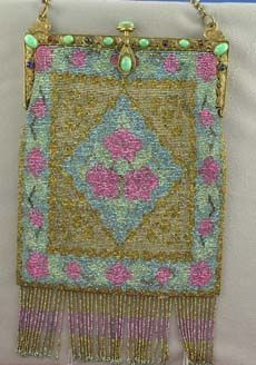 A steel beaded purse with bright colors on a jeweled metal frame with matching stones. Colors include pink, turquoise and gold. There are two small swans at the top of the handle that support a chain. Original lining.