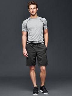 Il porte un t-shirt gris, des shorts noirs et des baskets noirs.