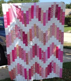 "Jelly roll quilt - Quilted by Stephannie Brown. Pretty in Pink - Strawberry Hills. Pattern is Notting Hill by Joel Dewberry, adapted to use a jelly roll of main color and a jr jelly roll of white. Pink strips cut to 11"", center white strips 6.5"", staggering white strips 2.5, 4.5, 6.5 & 8.5"" at top and bottom. Materials used: pink jelly roll - 40 different fabrics and white jr.jelly roll - all one fabric. Quilt pattern on Free Spirit Fabrics under Free Patterns."