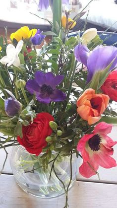 Voorjaarsboeket van ranonkel, anemoon, tulpen, fresia, iris, kersenbloesem en bosbes