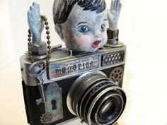mixed media art assemblage sculpture from vintage camera and baby doll