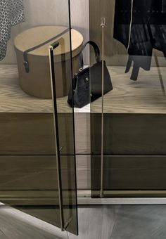 Shakedesign_Wardrobes_Freedom wardrobe, structure in T49 cenere, bronze glass doors without frame, light bronze metal details and handles in burnished brass. Equipped with wooden drawers and metal coat-hangers, integrated led lighting