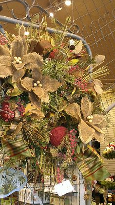 Burlap pointsettias decorate a wreath affixed to an old garden gate which is suspended.