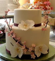 Ivory fondant with pale pink branches of cherry blossoms and white phaleonopsis orchids. By Something Sweet by Michelle.