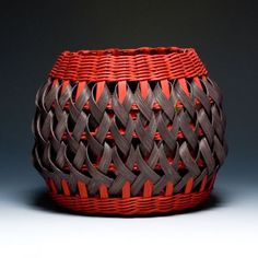 Penland Pottery Basket - Black & Red  by Billie Ruth Sudduth.      Materials: Baskets are made with european cut reed splints split oak and seagrass. Handles are carved on a shave horse using a draw knife. Dyes used include crushed black walnut hulls henna madder and iron oxide.