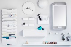 A selection of white storage products including a mirrored storage cabinet and a wall-mounted filing rack, a clock and light on a white wall with homey accessories for decoration.
