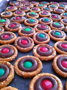 Salty and Sweet Christmas Treat: Pretzels rings and Hershey's Kisses in an oven at 200°-225°, press in M&Ms when the Kiss is softened (I love the idea of trying this with Rolos and pecans, too!)