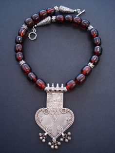 by Luda Hunter   'Heartfelt'. Old large heart shaped silver pendant from Rajasthan India is surrounded with old African copal amber trade beads with 9.25 Bali silver beads & clasp   550$