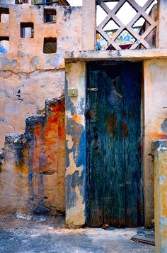 Harlequin Years - By Anna Wacker  An explosion of wild colours on the door and walls of a village house.  Photo taken in Karpathos, Greece