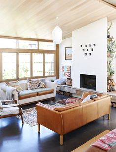 Pops of color against stark white, small patterned rug against dark wood floor, low clean-lined furniture with large, open, modern windows, stacked firewood, shelving unit full of plants