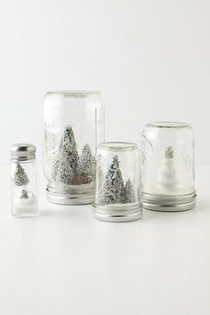 from Anthropologie. So easy. Just glue an item to the top of the mason jar, add fake snow, screw on the top, and turn over.