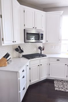 Finished kitchen renovation   Wall: Sherwin Williams Requisite Gray Cabinet paint: Behr Ultra Pure White Counter tops: Corian Rain Cloud