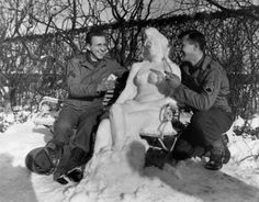 "Cpl. Bernhard Butnik, of Cleveland Heights, Ohio, and Sgt. Richard Goodbar, of Russellville, Arkansas, offer ""Agnes"" their snow woman, cigarettes and a ""coke."" January 14, 1945"