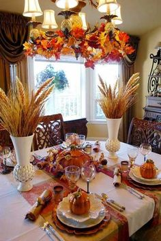 Thanksgiving Decor Dining Rooms | wheat heads in white vases and chandelier decorated with fall leaves