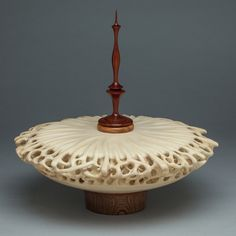 Turned and hand-carved wood vessel by Mark Doolittle.  Woods are Bubinga (base), Linden (vessel), African Padauk (finial). [The amount of carving in this piece is conducive to Linden (basswood)]