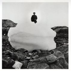 "The caption reads: ""View of a person sitting on a large ball of snow on rocky ground."""