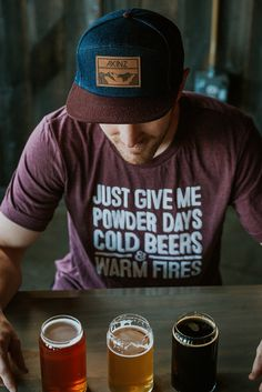 Winter is here and there has been a small shift in our priorities... Just Give Me Powder Days, Cold Beers & Warm Fires. White print on a maroon heather
