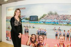 Olympic gold medal winning Katherine Grainger, standing beside the River & Rowing Museum montage of 2012 Olympic rowers.
