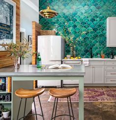 "Light and understated was never the personality of this loft—or its owner—says interior designer Gina Sims, who amped up this plain kitchen with layers of bold features. Homeowner Cati Teague specified ""awesome and green,"" which sent Sims on a hunt for the perfect backsplash tile."
