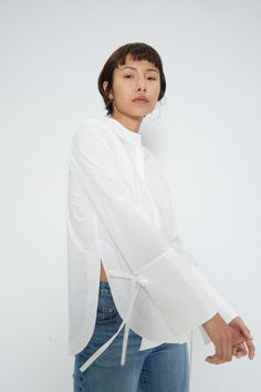 Angie White Shirt  Product Details:Long sleeve button down shirt with Mandarin style collar. Over sized cuff with tie details and shapes hem. Material