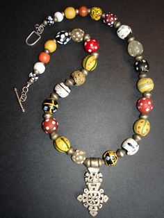 Designed by Luda Hunter | Necklace. An old hinged Ethiopian silver cross is surrounded by a mix of antique and rare African glass trade beads including skunk beads, medicene man beads, end of day beads, and fancies.
