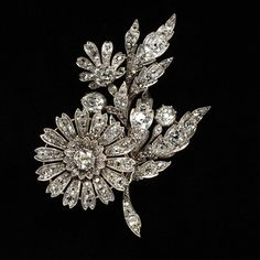 Ornament in the form of a floral spray consisting of a chrysanthemum flower, a half-opened flower and two buds with seven leaves. Brilliant-cut diamonds set in silver. circa 1880