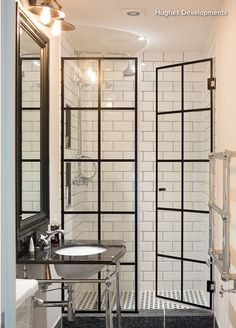 The shower doors in this stylish monochrome bathroom were made to look like Crittall windows by adding metal flashing to standard shower doors.