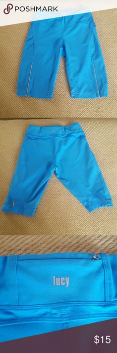 Lucy Workout Shorts These shorts have only been worn a few times and almost look brand new. They are a Bermuda short style yoga fit. There is some reflective lining along the front thigh. It features a small zipper back pocket (shown in the above pictures) and some drawstring on the inside lining for a better fit. The material is super soft and the color is very vibrant and blue. Make an offer. Lucy Shorts Bermudas