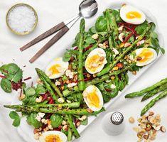 Passa på att njuta av sparris. Den här aptitretande salladen med krispiga gröna blad smaksätts med en dressing av olivolja och citron. Grillad sparris och ägg gör den matig och nötterna ger en god knaprighet. Ibland är det enklaste det allra godaste!