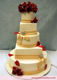 Swarovski crystal brooches and cascading rose petals highlight this five tier wedding cake. Flavors included alternating layers of red velvet cake with lemon cream cheese and chocolate cake with vanilla buttercream.