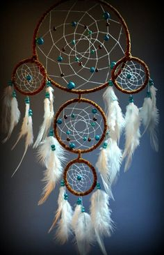 This one might look complicated but it's actually like doing a normal one. However, you'd have to create 5 circles with looped strings here in different sizes and attach them to one another. Then you can proceed with strategically hanging the feathers and beads.