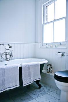 Das Elternbad ist vom Historismus geprägt. Wie in den übrigen Räumen wurden die Wände hell gestrichen, und die sanitäre Einrichtung dominiert in Schwarz und Weiss.