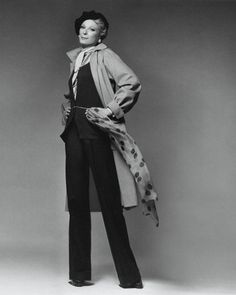 ca. January 1974, New York, New York, USA- Nan Kempner wearing camel hair coat and cuffed plain-front pants by Yves Saint Laurent, with cashmere sweater and chain belt with tiger eye by Halston; a beret, and holding a long print silk scarf, — Image by  Condé Nast Archive/ CORBIS