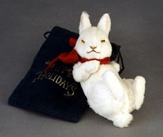 "RJW - Christmas Dreams- 5 1/2"", white mohair plush, fully jointed, embroidered features, red felt bow. 	Date of Release: 2002 Private Ltd. Ed. 50. The lowest numbers were given to R. JOHN WRIGHT employees in veleteen bags (shown). The higher numbers were given to top retailers and suppliers in green gift boxes. All included a certificate of authenticity signed by both Susan and R. John Wright."