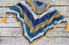 This crochet triangle scarf looks like the granny or bobble stitch, but it's actually the bead stitch. The tassels complete this modern scarf. Free pattern and video tutorial!