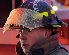 Schenectady firefighter/paramedic Adam Colvin's helmet is covered in ice after a neighboring house exploded when a gas main was severed by a construction worker in Schenectady, New York, on January 4, 2012. All occupants were accounted for, and 3 alarms were sounded to control the blaze. (AP Photo/The Daily Gazette, Peter R. Barber) #