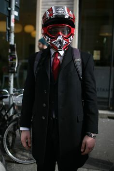 What They Are Wearing: A dirtbike helmet and a nice suit. Only in Italy.  Out and About at Milan Fashion Week '12. Photo by Kuba Dabrowski for WWD.
