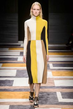 The geometric patterns of the runway carpet mirrored the graphic knit color blocks of high-neck knit dresses and wide bands of color that defined the hems of pleated skirts and dresses.    - HarpersBAZAAR.com