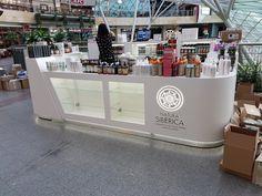Nowoczesna wyspa handlowa z corianu, z eleganckim podświetlanym logo, szklanymi półkami. Wyspa wykonana z kompozytu i lakierowana.