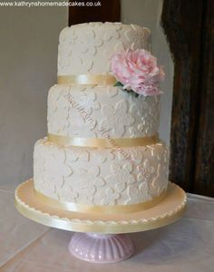 Ivory 3 tier wedding cake with embossed details and large pale pink sugarcraft rose